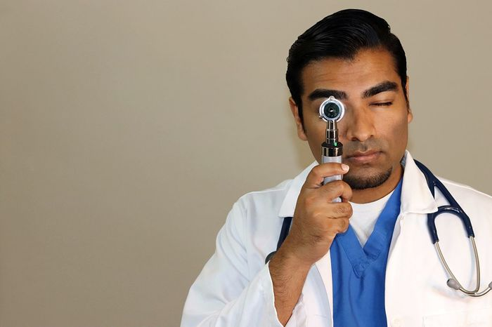 Young handsome doctor in blue scrubs and white lab coat looking through otoscope Asian  Blue Dentist Doctor  Emergency Equipment Face Mask Gloves Health Healthcare And Medicine Hospital Indian Lab Coat Medical Medicine Nurse Procedure Scalpel Scrubs Spanish Stethoscope  Surgeon Surgery Uniform White Color