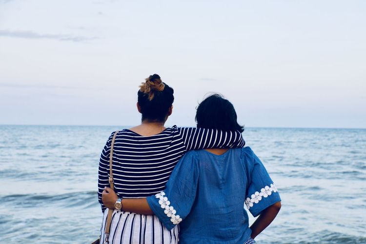 Rear view of female friends standing at beach