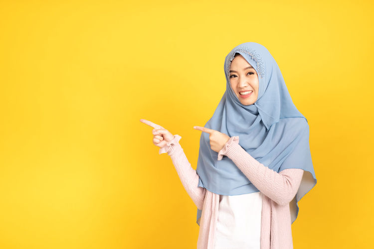 Smiling young woman standing against yellow background