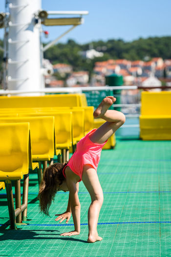 Girl doing cartwheels on Croatian ferryboat in Mali Losinj. Little girl is activly doing cartwheels on vacation. Concept of active children, fitness and healthy lifestyle. Childhood Child Real People Leisure Activity Outdoors Girl Croatia Active Children Family Excercising Fitness Activity Leasure Activity Cartwheel Cartwheels Gymnastics Mali Lošinj Ferry Ferryboat Jadrolinija Backgrounds Town Vacations Hollidays