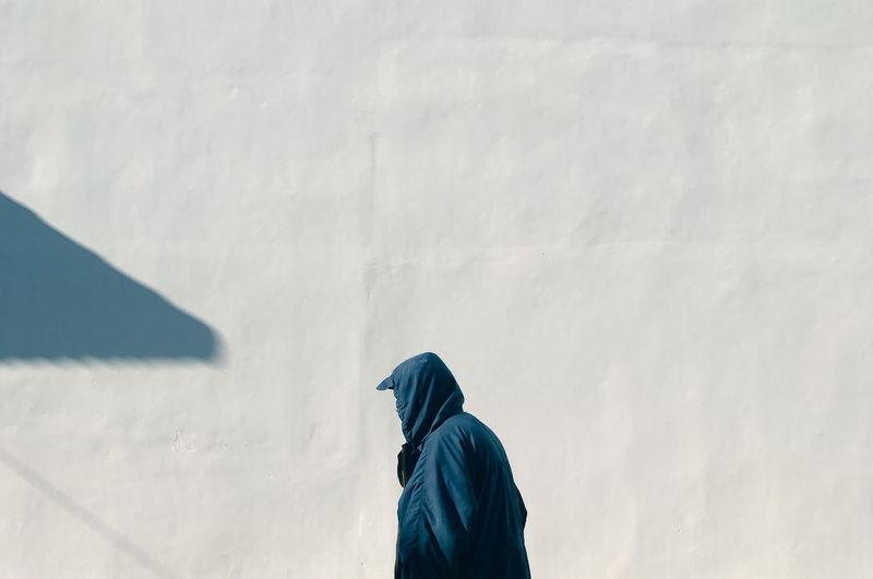 Man wearing hoodie standing against wall