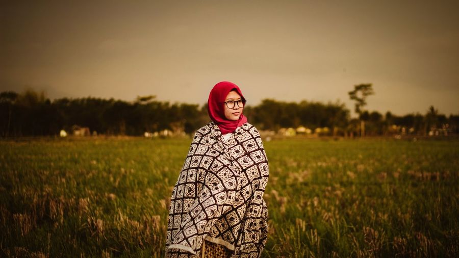 Young woman wearing hijab while standing on grassy field against sky during sunset