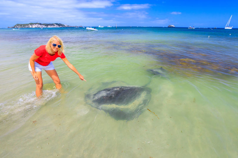 Happy blonde tourist woman pointing at Australian Eagle Ray in Hamelin Bay, Western Australia. Hamelin Bay is one of the best places in Australia to spot wild sting rays up close. Australia travel. Eagle Ray Eagle Rays Sting Ray  Australia Australian Beach Sea Hamelin Bay Water Fish Marine Marine Life Coral Reef Woman Girl Leisure Activity Lifestyles Land One Person Sky Beauty In Nature Nature Real People Horizon Over Water Day Horizon Scenics - Nature Full Length Child Women Outdoors