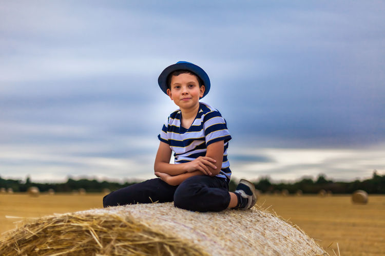 Portrait Of Cute Boy Sitting On Hay Bale Against Cloudy Sky