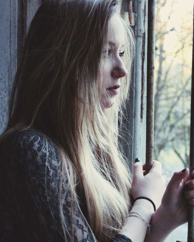Side view of thoughtful woman looking through window