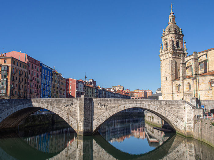 Arch bridge over canal amidst buildings against sky in city