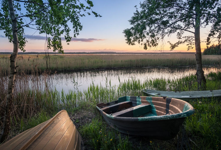 Scenic landscape with rowboats at peaceful summer evening in Hyvinkää, Finland. Atmospheric Mood Birch Blue Boat Calm Colorful Dawn Evening Finland Freshness Glow Green Lake Landscape Night Peaceful Rowboat Scenics Sky Summer Sunlight Sunset Tranquility Tree Water