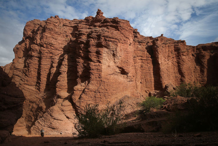a motorcycle through huge rock walls reddish in Salta Argentina during the Dakar 2016 Argentina Arid Climate Dakar Day Desert Eroded Extreme Sports Extreme Terrain Geology Motorcycle Physical Geography Rock Rock Formation Salta, Argentina Stone