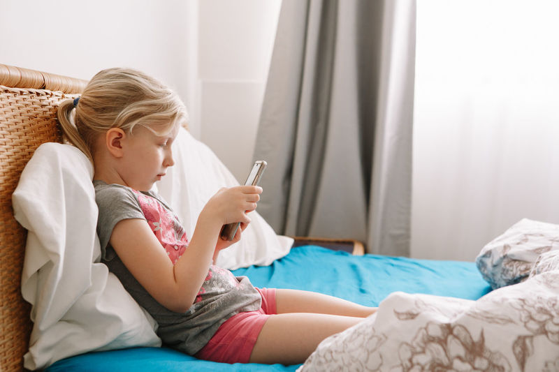Side view of girl using phone while sitting on bed at home
