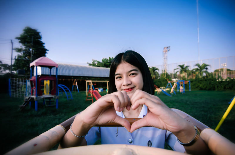 Portrait of young woman making heart shape against sky at playground