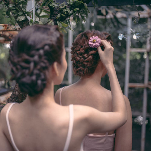 Rear view of woman adjusting flower on bride hair