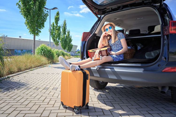 Portrait Of Teenage Girl With Guitar Sitting In Car Trunk By Luggage