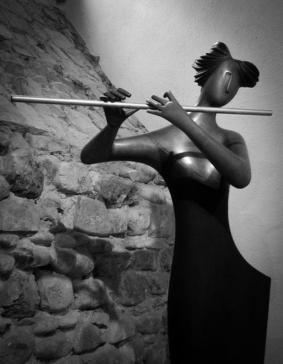 Flute player Suonatrice di flauto Gianfranco Giorni Anghiari, Toscana Gianfranco Giorni Females Flute Player Holding Indoors  Leisure Activity Lifestyles Rear View Rock Sculpture Solid Standing Three Quarter Length Wall - Building Feature