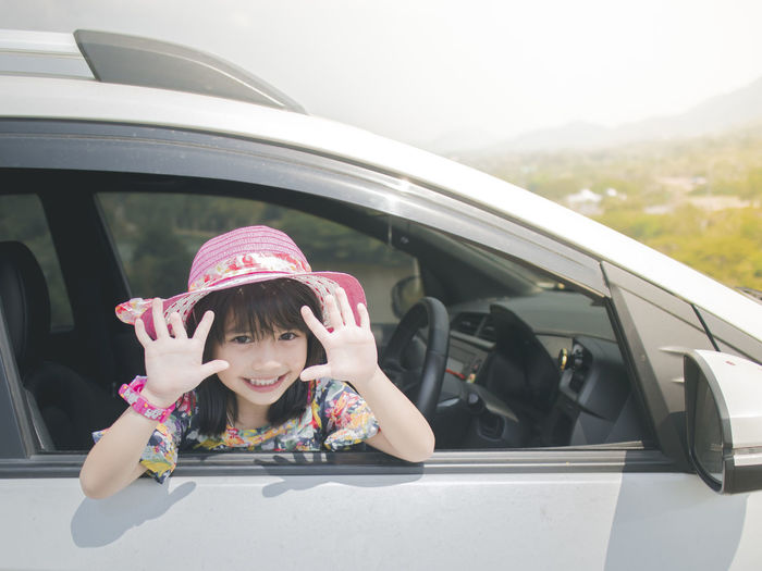Portrait of a smiling girl sitting in car