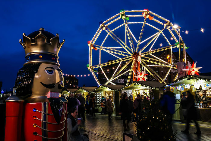 Victorian Christmas Costume Market Stall Retail Place Outdoors Dusk Twilight Cityscape Illuminated Night Fairground Soldier Nut Cracker Carnival Crowds And Details