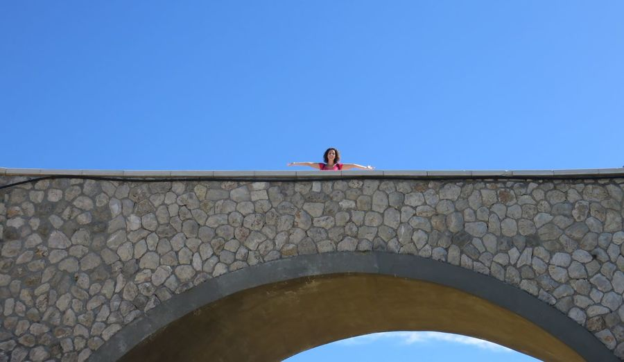 Low angle view of woman standing on bridge against clear blue sky