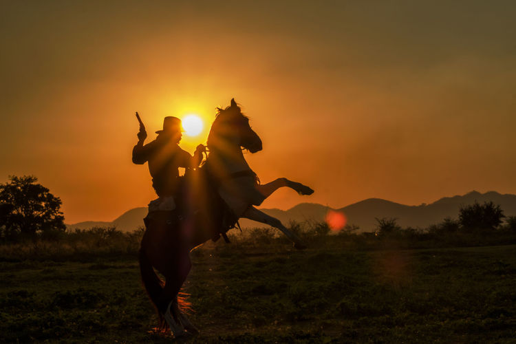 Silhouette person holding gun while horseback riding on land against sky during sunset