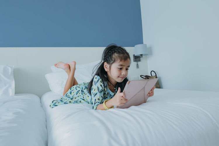 Little girl playing ipad table on bed