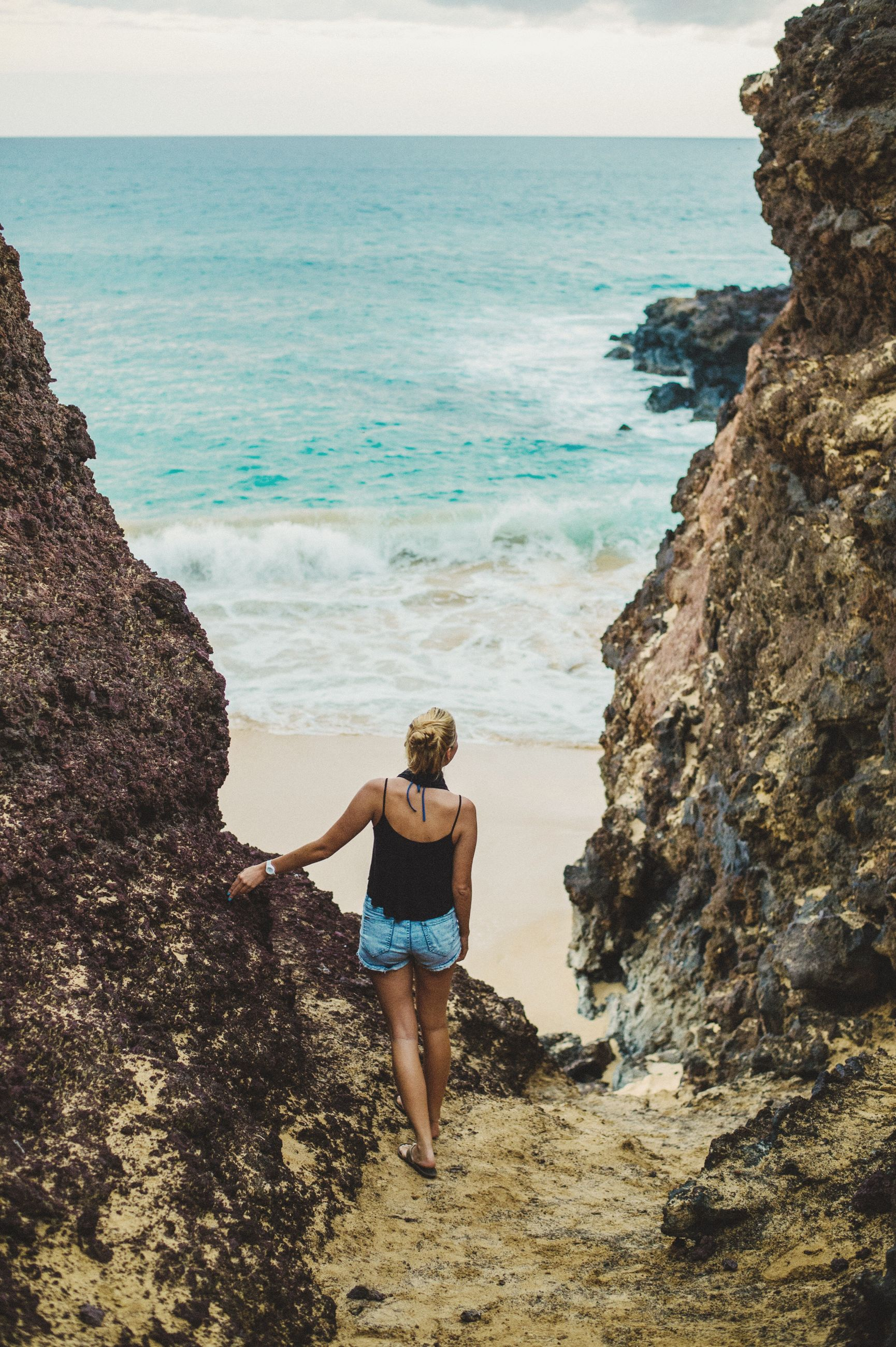 sea, horizon over water, beach, water, shore, lifestyles, leisure activity, full length, beauty in nature, scenics, tranquil scene, tranquility, vacations, nature, sky, rock - object, idyllic, casual clothing, day, outdoors, rock formation, remote, coastline, blue