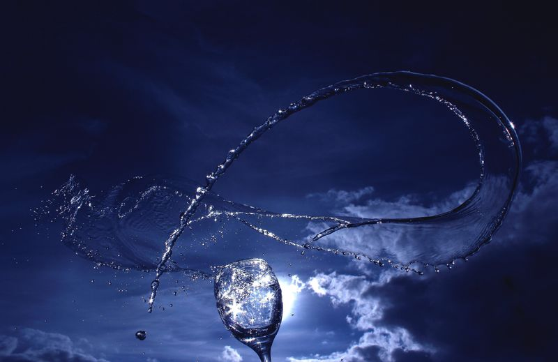 Water Splashing From Wine Glass Against Cloudy Sky