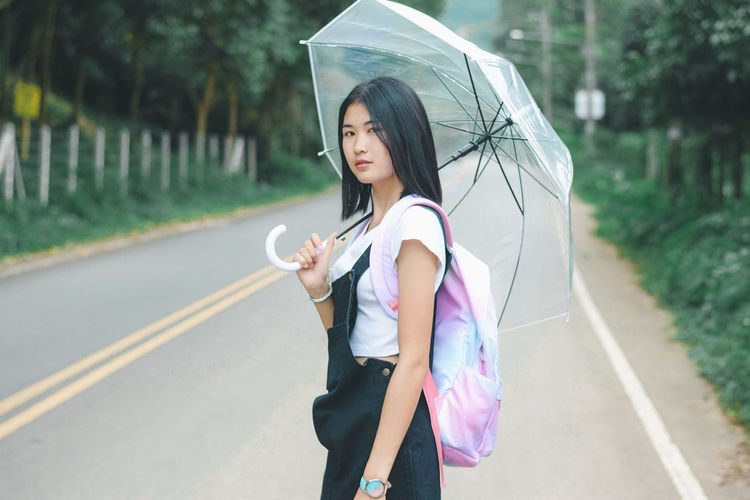 Woman holding umbrella while standing on road