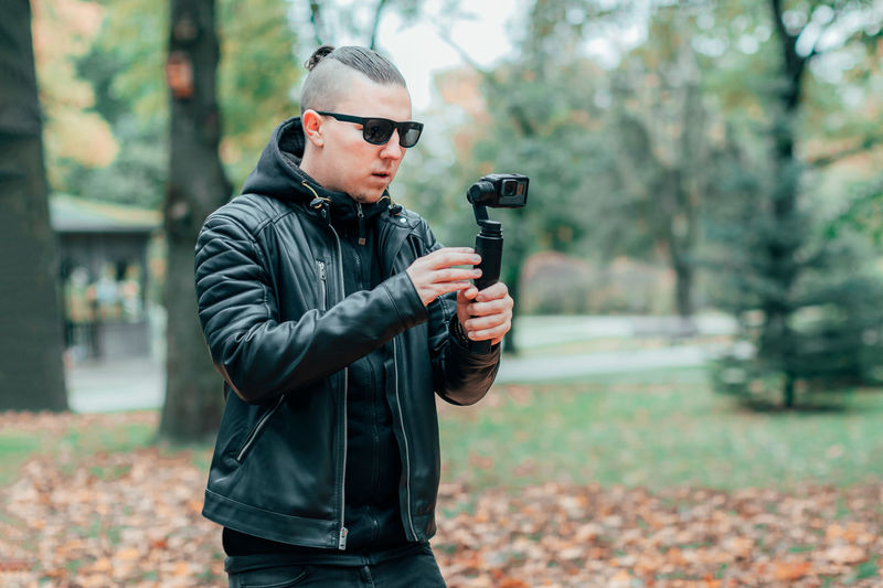Young man wearing sunglasses filming in forest