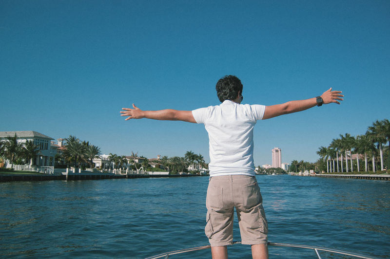 Rear view of man with arms outstretched on boat in lake