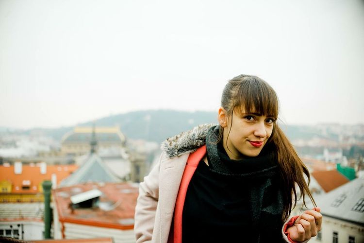 Portrait of smiling young woman in city against sky