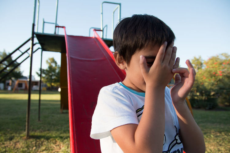 Boy covering face at playground