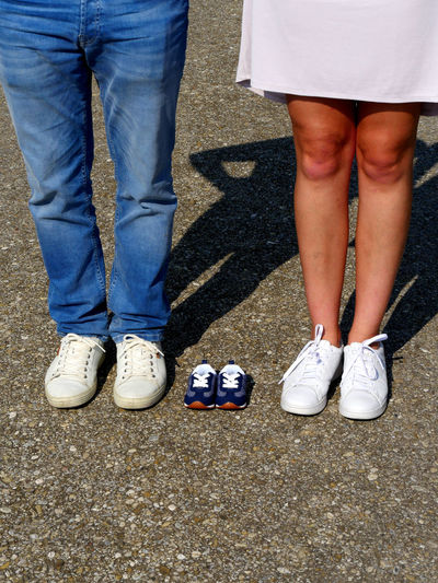 Low section of couple standing by baby booties on road
