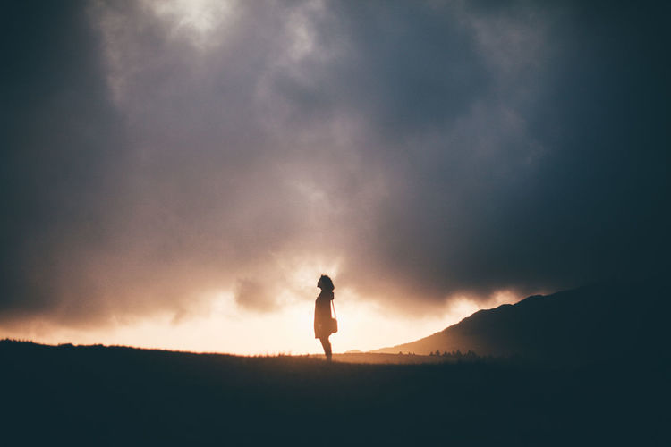 Silhouette Woman Standing On Landscape Against Clouds