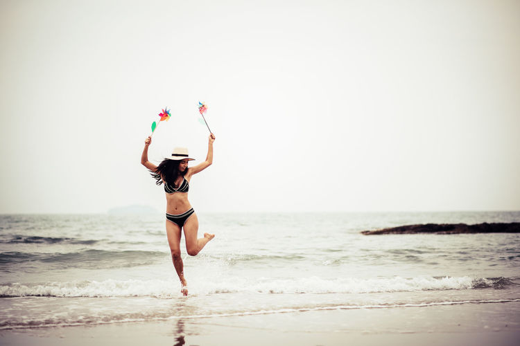 Sea Beach One Person Land Full Length Horizon Over Water Human Arm Lifestyles Arms Raised Leisure Activity Horizon Water Sky Rear View Young Adult Limb Beauty In Nature Women Human Limb