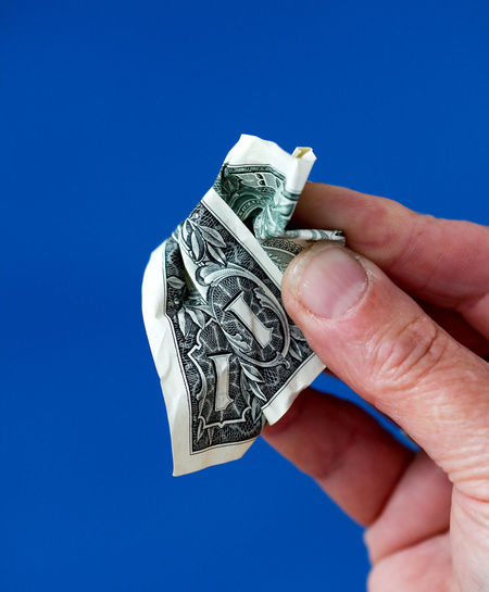 Cropped hand holding crumpled paper currency against blue background