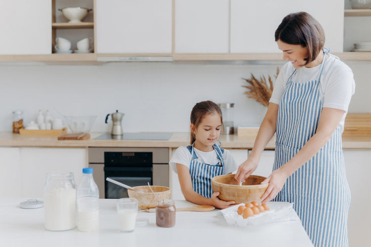 Mother and daughter in bowl at home