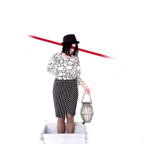 Woman sitting on umbrella against white background