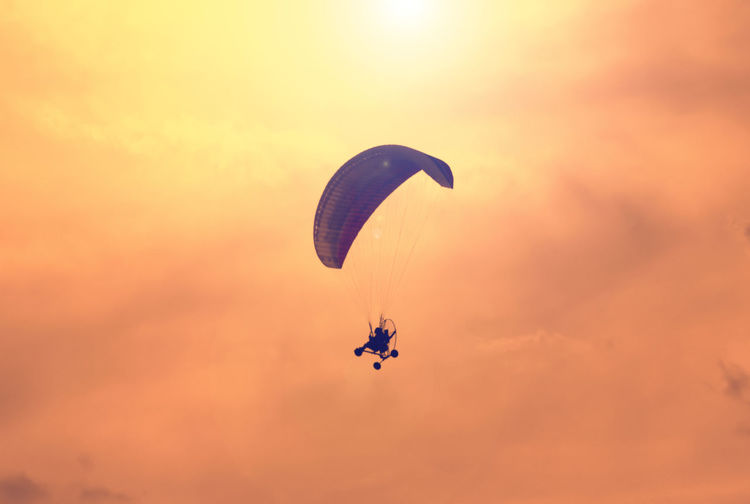Low angle view of silhouette person paragliding against sky during sunset