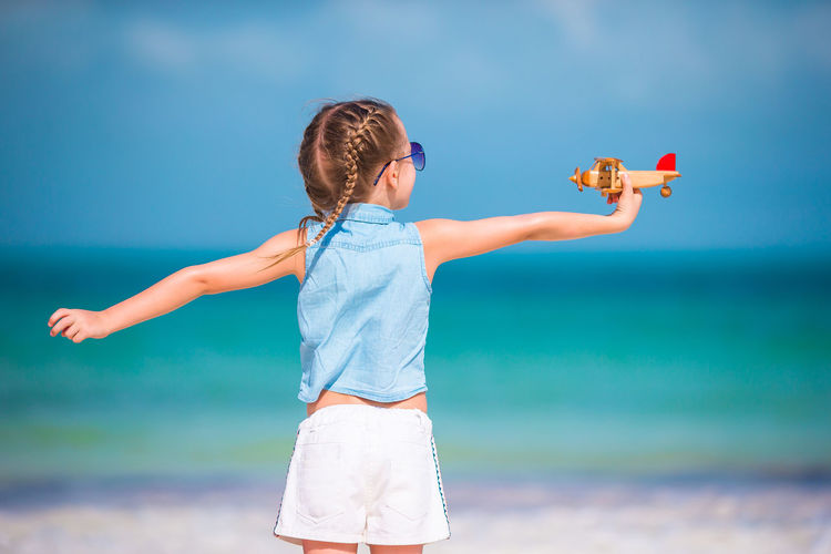 Low angle view of girl with arms raised against sky