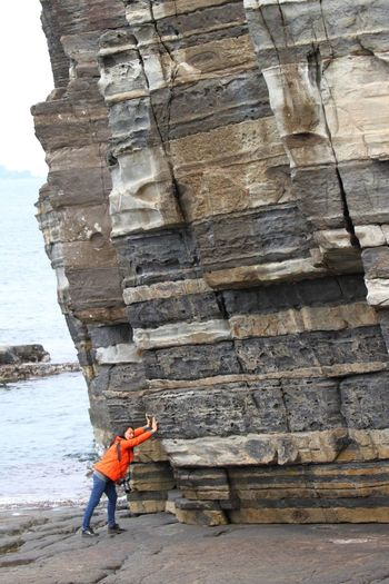 Optical illusion of woman pushing cliff at beach