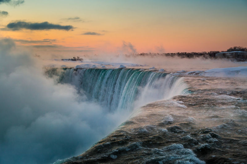 Scenic View Of Waterfall Against Sky At Sunrise