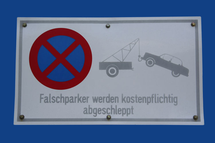 No Parking - Text in English: Cars parking here will be tow away Blue Background Close-up Communication Falschparker Forbidden German Germany Halteverbot Isolated No No Parking No Parking Sign No Stopping No Stopping Sign Parken Verboten Parking Road Sign Script Sign Street Sign Text Towing Traffic Traffic Sign Western Script