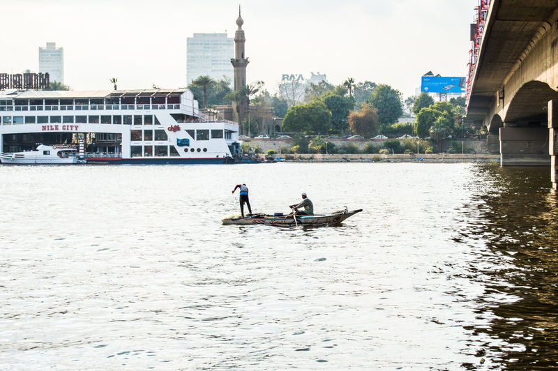 Men sailing on boat in city against clear sky