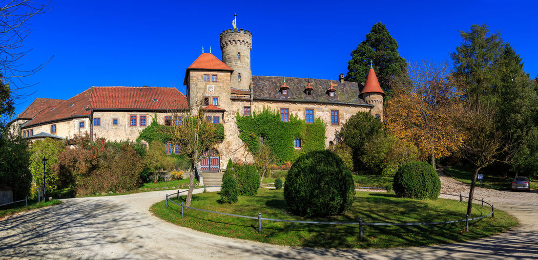 COBURG, GERMANY - CIRCA OCTOBER, 2017: Schloss Hohenstein, a castle in Coburg, Bavaria, Germany Architecture, Castle, Coburg, Editorial, Europe, European, Garden, Germany, Historic, Landmark, Old, Outdoors, Palace, Park, Plants, Stone, Street, Traditional, Travel, Urban Building Exterior Architecture Built Structure Tree Plant Sky Building Nature Clear Sky Blue The Past History Day No People Footpath Travel Tower Travel Destinations Outdoors Growth Hedge