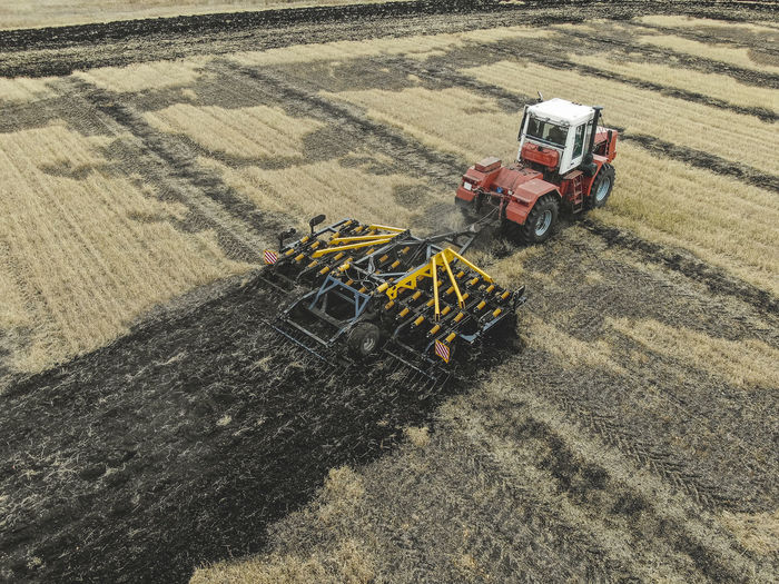 Aerial view of a modern tractor plowing dry field, preparing land for sowing Aerial Agriculture Field Tractor Farm Ground Soil Countryside Combine Machinery Motion Working Plowing High Angle View Rural Scene Agricultural Machinery Nature Agricultural Equipment Mode Of Transportation Transportation