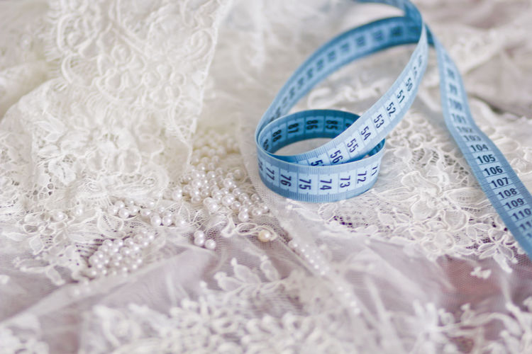 Close-Up Of Tape Measure On White Dress