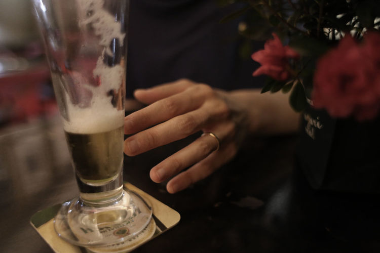 Cropped image of person by beer glass
