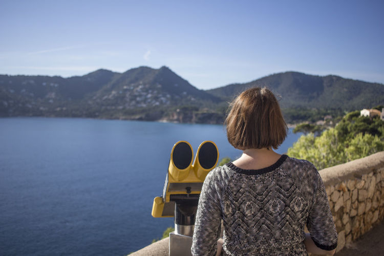 Rear view of woman standing by coin-operated binoculars at observation point against mountain
