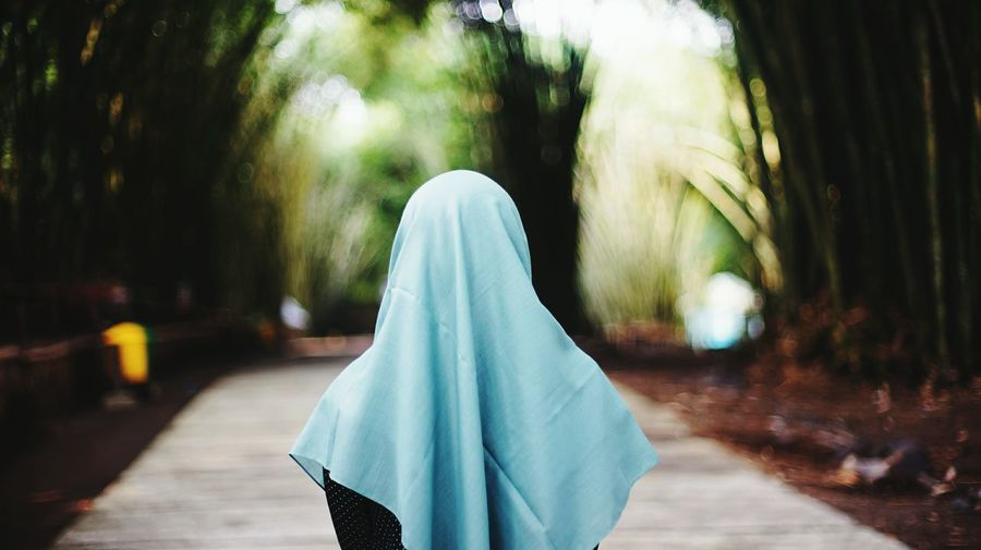 Rear view of woman wearing hijab while standing in park
