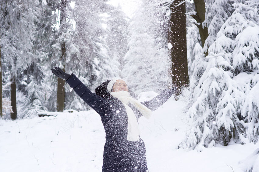 Adult Adults Only Arms Raised Cold Temperature Day Enjoyment Fun Happiness Human Arm Leisure Activity Mid Adult Motion Nature One Person One Woman Only Only Women Outdoors People Real People Side View Snow Standing Warm Clothing Winter Young Adult