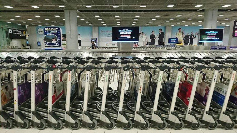 In A Row Large Group Of Objects Indoors  Airport Terminal Airport Airport Arrival Trolleys Baggage Cart Baggage Claim Luggage Trolleys Luggage Belt Baggage Trolleys Tv Screens Advertisement Airport Security Security Guard Luggage Collection