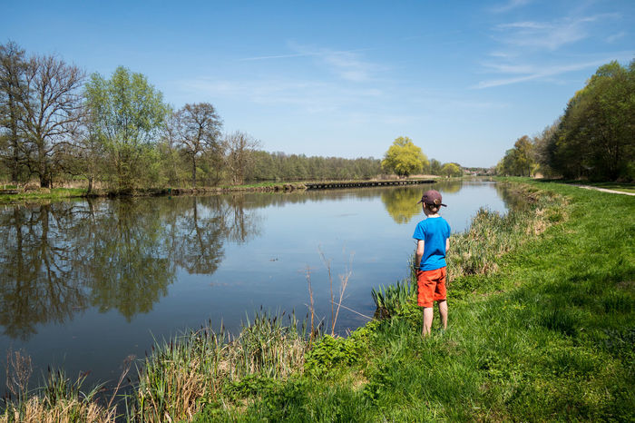 Canals And Waterways Canal Leisure Activity Weekend Activities Vacations Point Of View River Riverside Landscape Serenity Calm Quiet Moments Water Full Length Men Child Tree Lake Boys Childhood Walking Running Shorts Sports Clothing Shorts Countryside Grassland Son